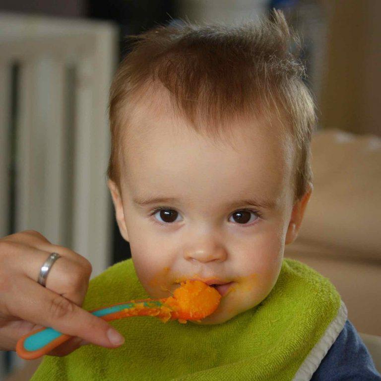 Bebe comiendo con cuchara, alimentación complementaria